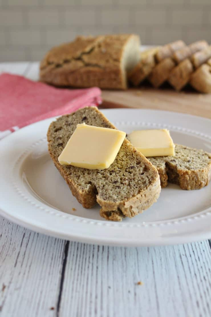 Slices of keto bread with slabs of butter on them on white plate with loaf in background