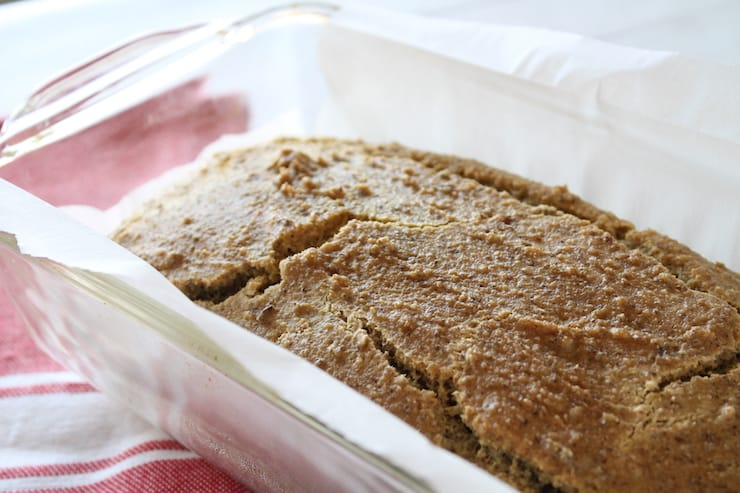 Close up of baked keto bread in clear loaf pan lined with white parchment paper with red dish cloth beside it