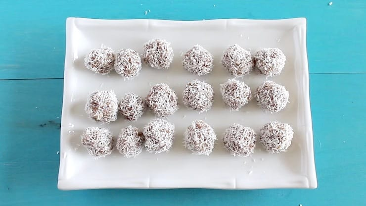 Finished rolled coconut date balls on a white rectangle plate on a blue table