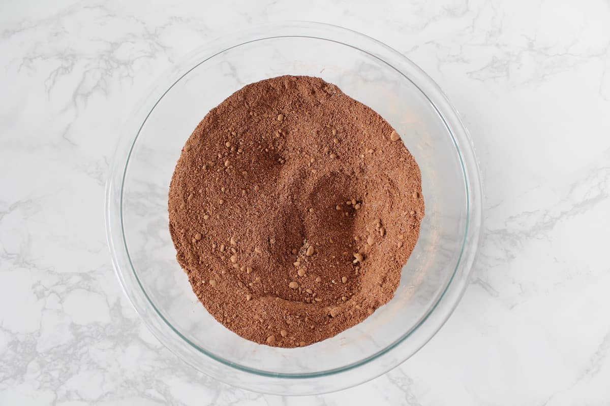 Overhead shot of clear bowl filled with brown powdered dry ingredients