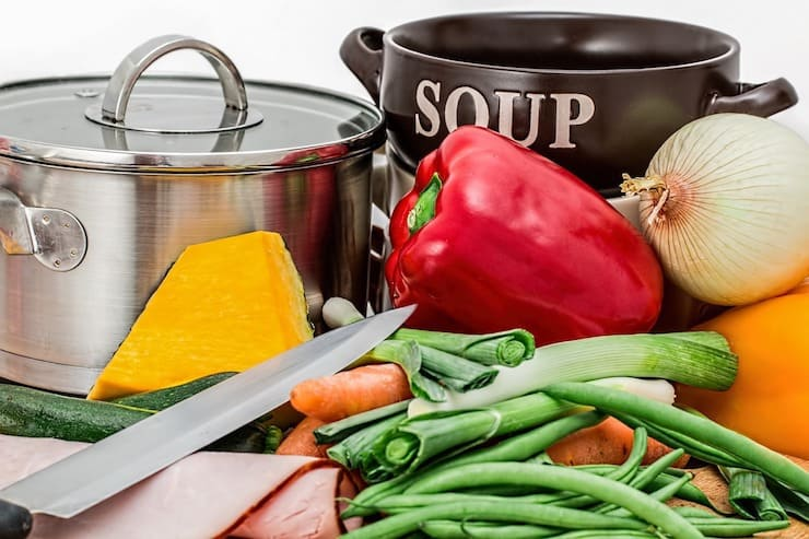 Collection of colorful vegetables with a knife beside it in front of a soup pot