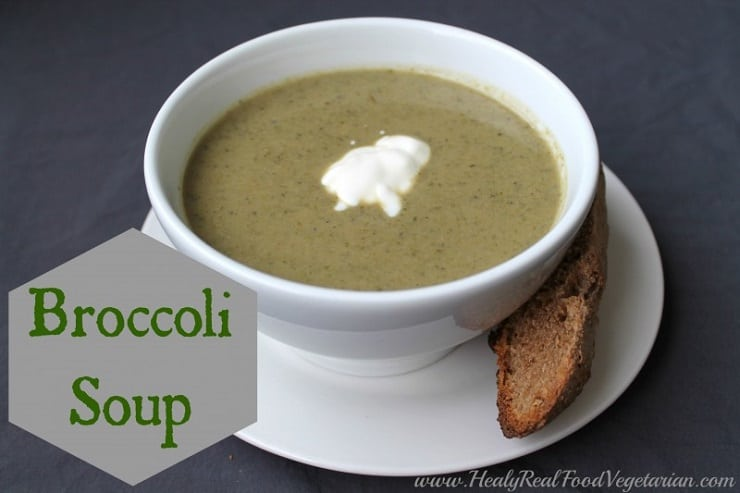 A close up of a bowl of broccoli soup in a white bowl with a slice of bread at the side