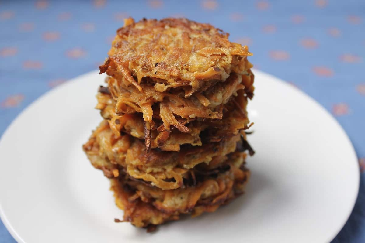 Closeup of several sweet potato latkes stacked on top of eachother on a white plate with a blue background