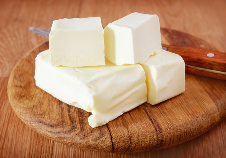 A photo of cubes of butter on a wooden chopping board