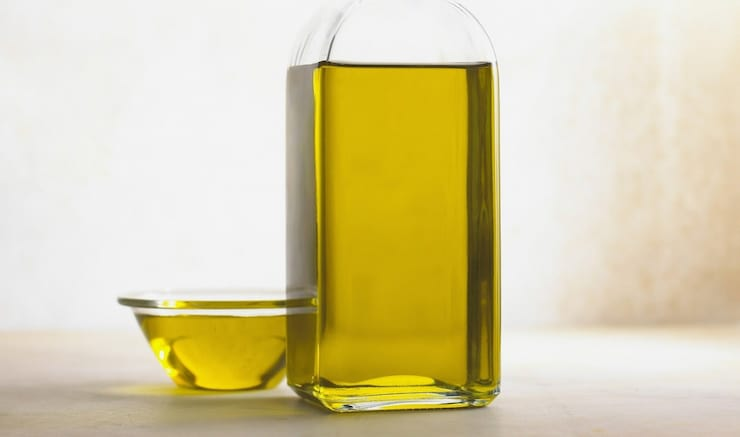 Clear glass bottle of olive oil with clear small bowl of olive oil next to it