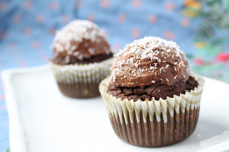 A close up chocolate grain free cupcakes sitting on a white plate and topped with shredded coconut