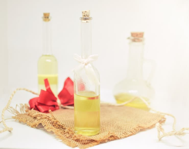 Tall glass bottles of oil on a burlap cloth
