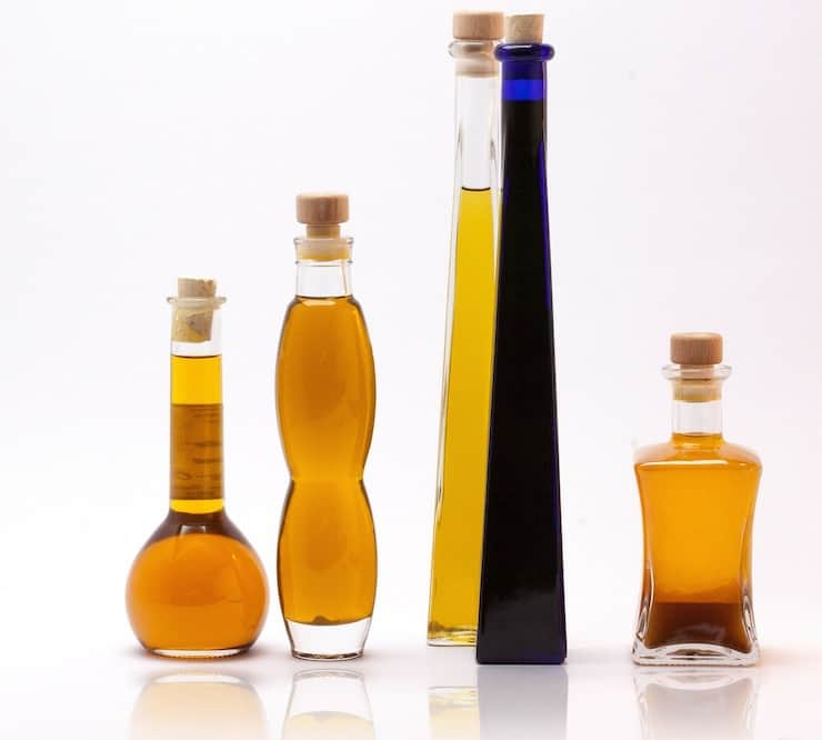 Four tall bottles of oil with one blue bottle with corks