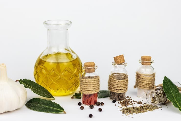 Clear glass bottle of oil surrounded by herbs and spices