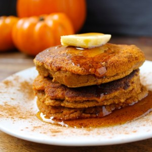 A stack of paleo pumpkin pancakes on a plate with maple syrup and pumpkins in the background