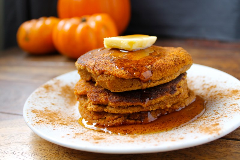 A stack of paleo pumpkin pancakes on a white plate drizzled with syrup and topped with a slice of banana