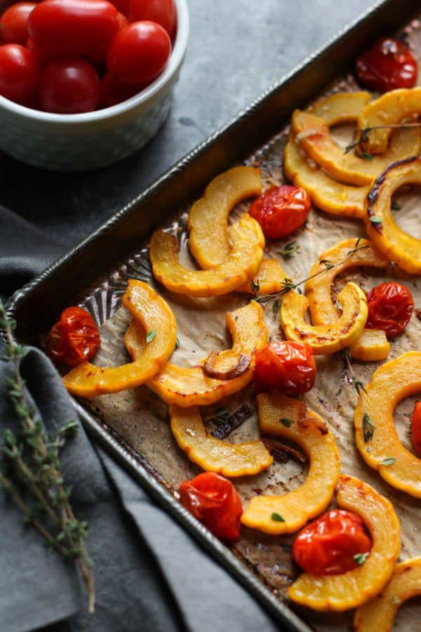 Roasted cut up squash and tomatoes on a tray