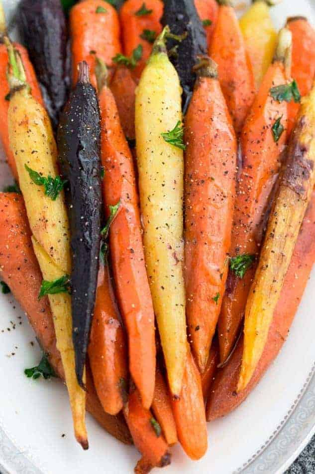 Whole roasted different colored carrots on a white plate arranged in the same direction on top of eachother with spices and herbs sprinkled on top