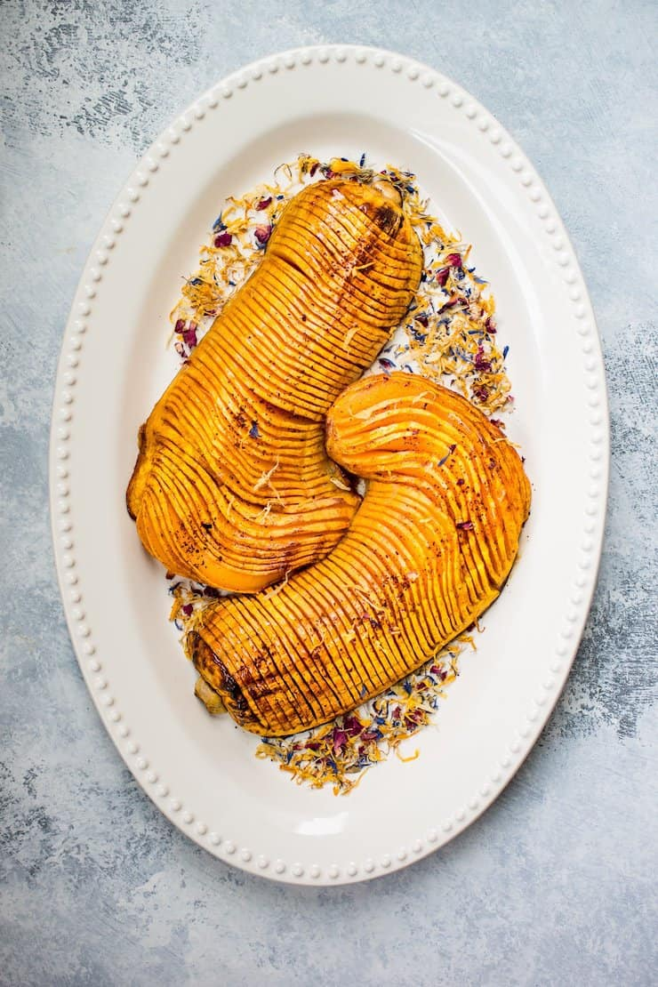 overhead view of hassleback whole butternut squash thinly sliced on a white platter on a grey surface