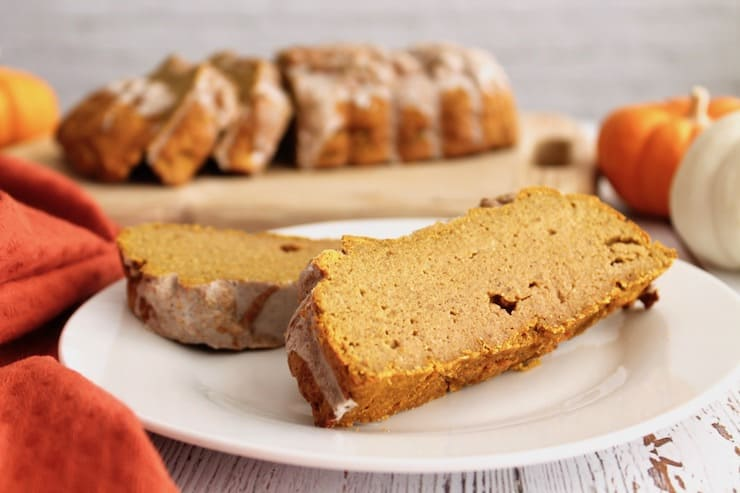 Close up up slices of healthy paleo pumpkin bread on a white plate with loaf in the background