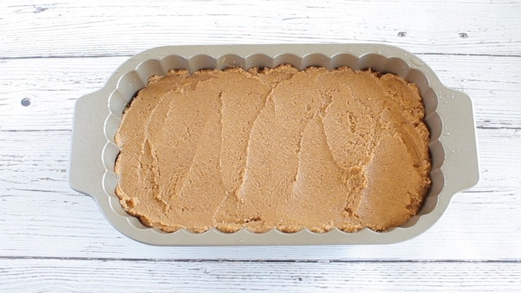 Uncooked paleo pumpkin batter in loaf pan on white wooden surface
