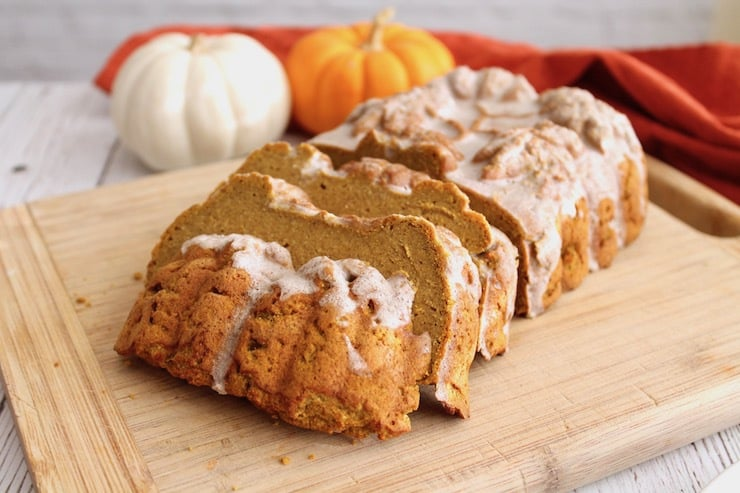 Sliced loaf of healthy paleo pumpkin bread with white icing on top on wooden cutting board with small pumpkins in the background
