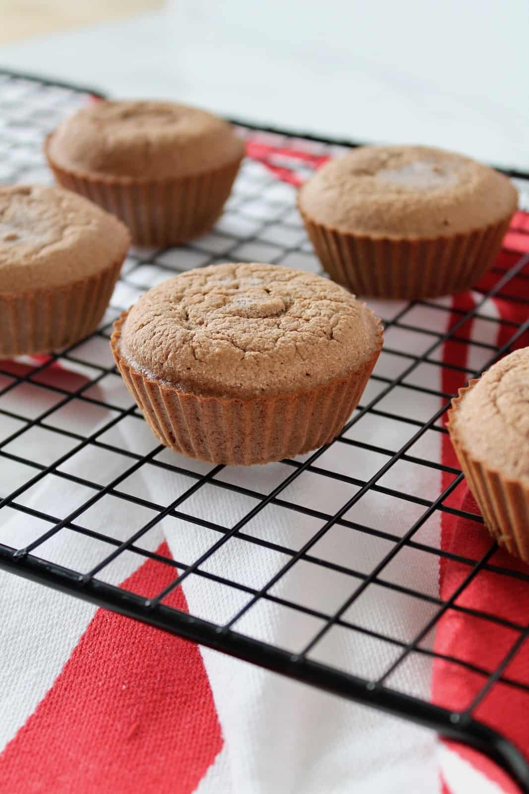 Keto chocolate muffins on a black wire cooling rack with red and white dish towel underneath