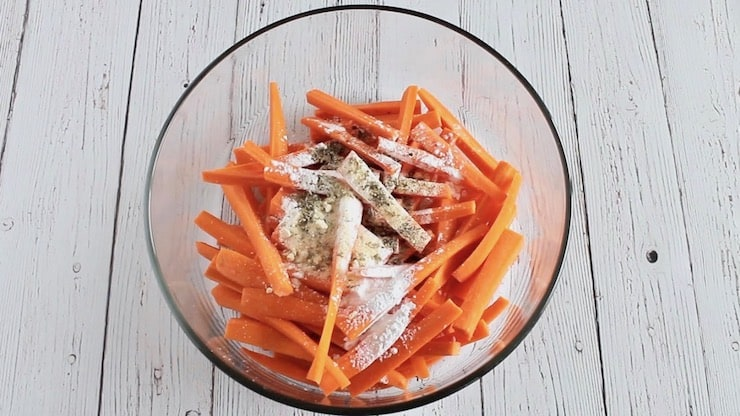 sliced carrots in a clear bowl with spices and flour on top of them