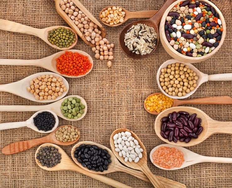 An overhead shot of wooden spoons filled with different grains and beans