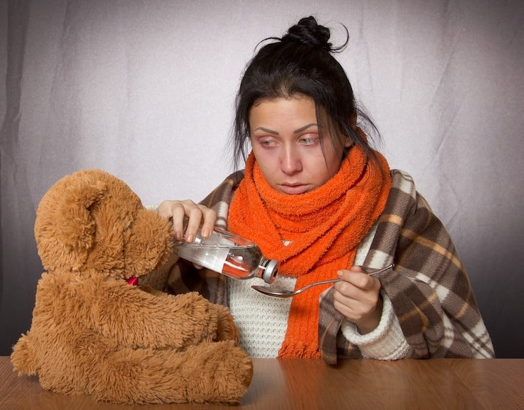 Sick woman with messy hair and oragne scarf pouring medicine onto a spoon