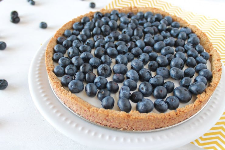 A whole blueberry tart on a white plate