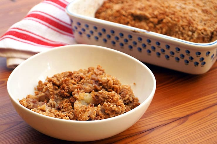 Apple crisp in a white bowl sitting on a wooden surface