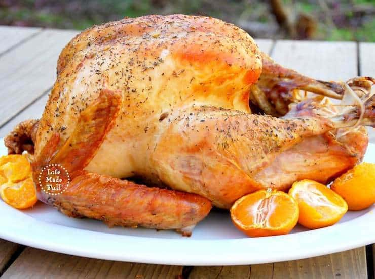 Roasted whole turkey on a white platter with mandarin oranges next to it