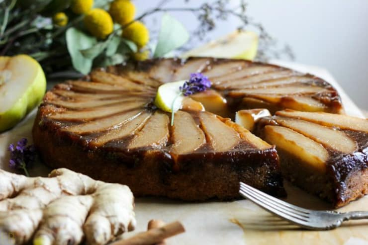A whole pear upside down cake with a slice cut out