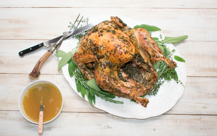 A roast turkey on a plate with herbs and gravy