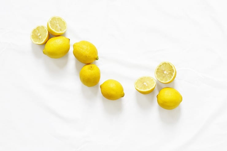 Several yellow lemons some sliced and some whole scattered on a white surface