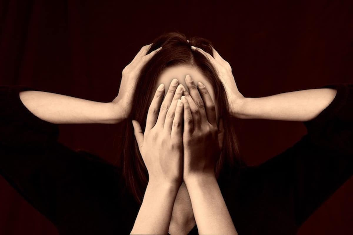 Woman covering her face with her hands with two hands on her head