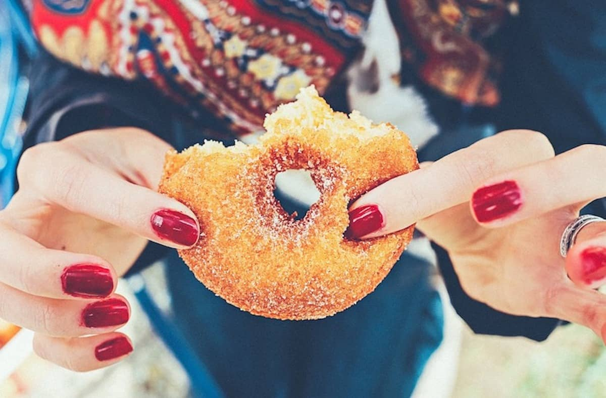 Close up of woman's hands holding a half eaten donut