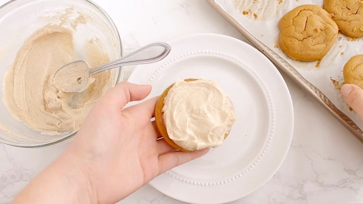A hand holding one cookie with filling on top of it over a white plate