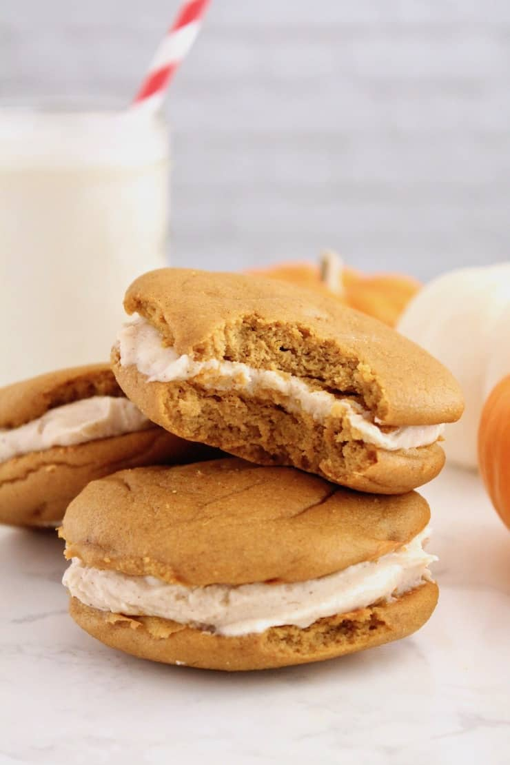 two paleo pumpkin whoopie pies on a white plate with one pie on top with a bite out of it