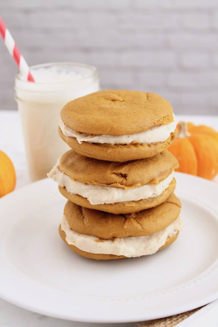 three paleo pumpkin whoopie pies stacked on top of each other on a white plate with pumpkins next to it