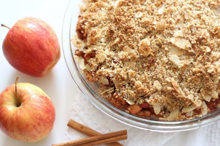 An overhead shot of a paleo apple crisp with apples at the side
