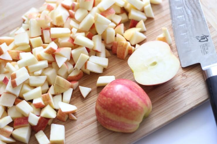 Chopped up apples on a wooden board for an apple pie filling