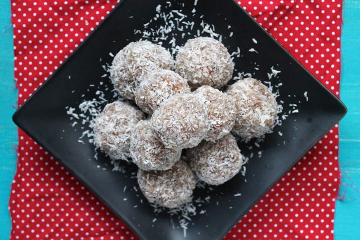 Coconut date balls in a pile on a black plate