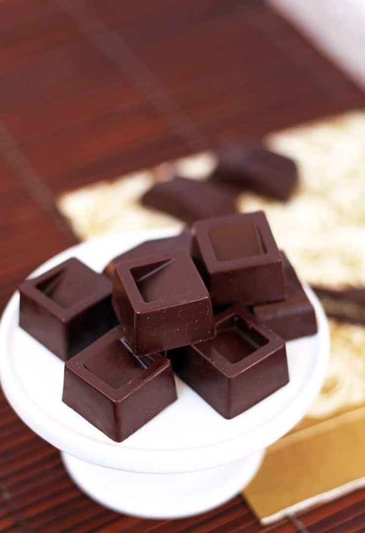 Dark chocolate squares stacked on a white plate