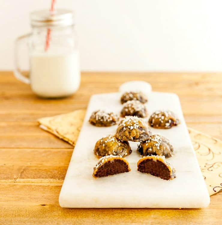 Samoa bombs on a white cutting board with a glass of milk at the side