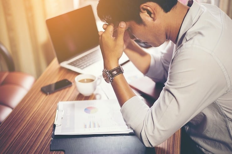 Stressed man at desk with head in hands