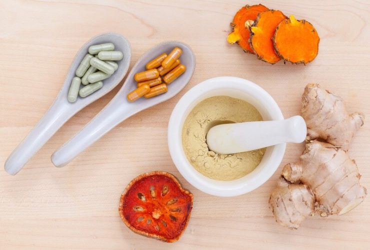 Mortar and pestle with powder and ceramic spoons with colorful capsules on a table