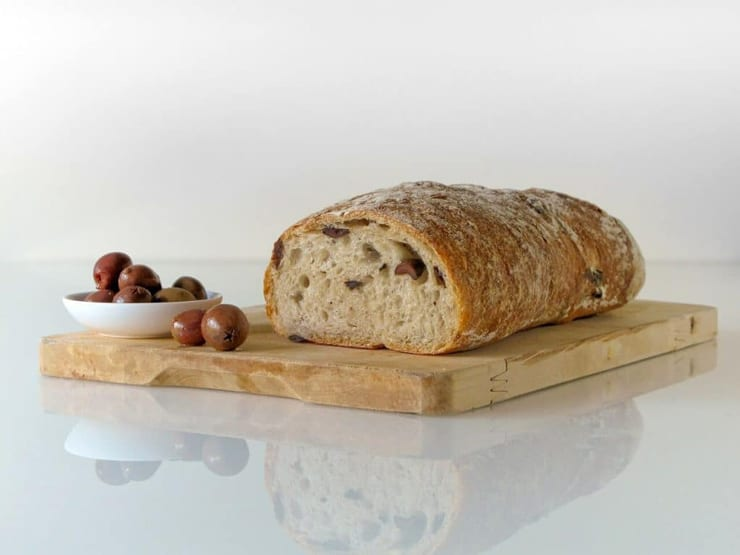 A loaf of ciabatta bread sitting on a wooden board with olives