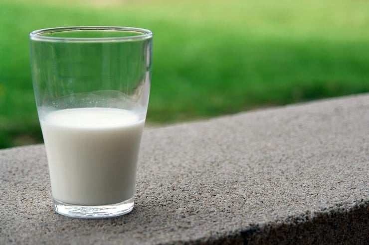 A half full glass of milk sitting on a wall outside
