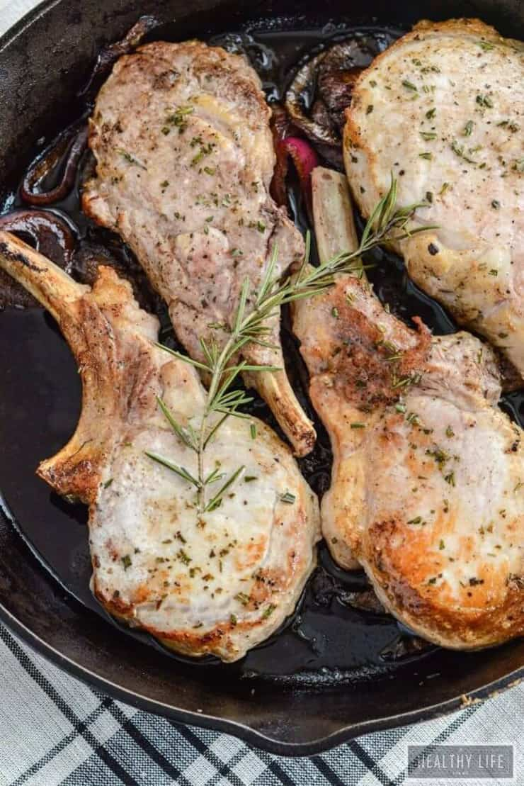 Balsamic pork chops in a pan topped with rosemary