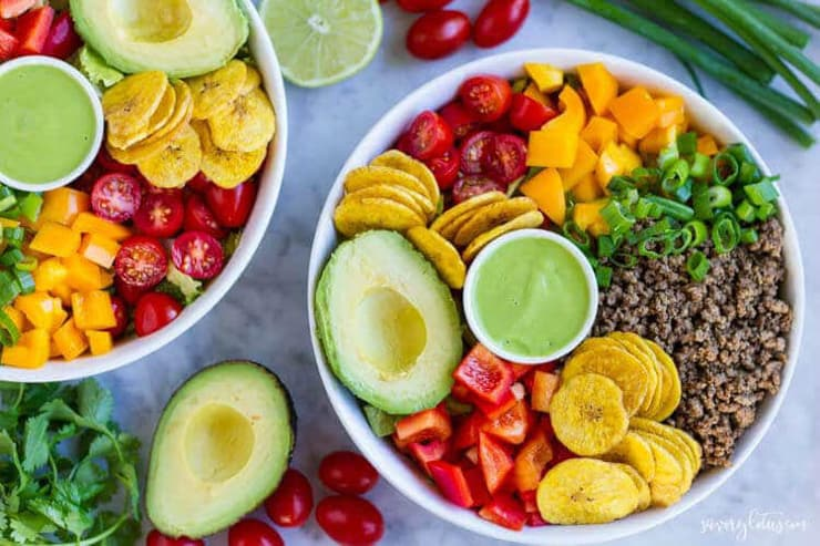 A bright and colorful taco salad bowl filled with fruit and veggies and green dipping sauce