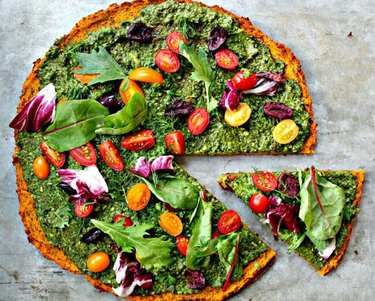 An overhead shot of a round healthy pizza crust topped with a green sauce, tomatoes and other vegetables