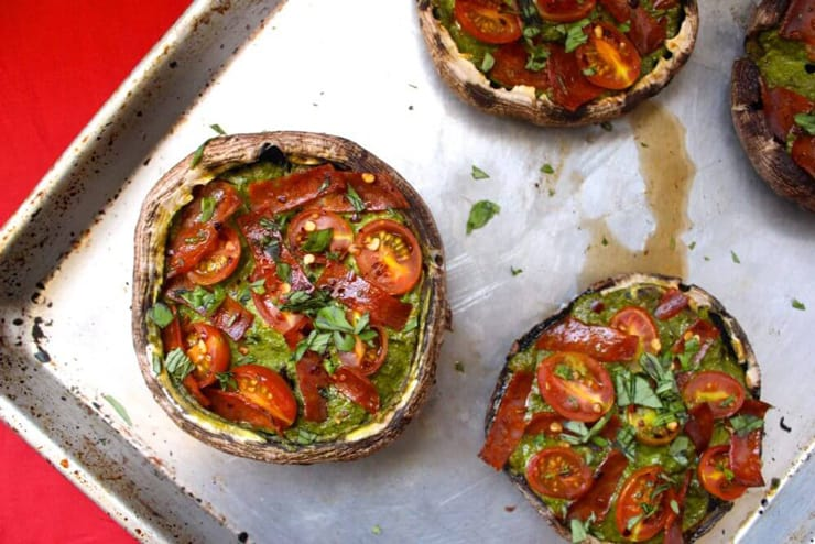An overhead shot of healthy pizza portobello mushrooms on a baking tray topped with tomatoes and pesto