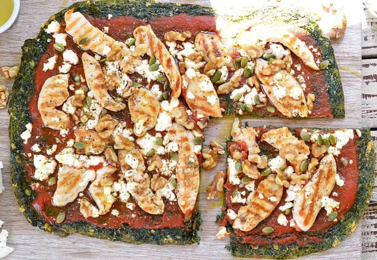An overhead shot of a healthy pizza made with a spinach crust sitting on a wooden surface with a corner slice cut out